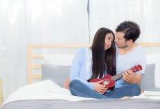 Νέα ασιατική παίζοντας ukulele χαλάρωση ζευγών με την ευτυχία και χαρούμενος στην κρεβατοκάμαρα στοκ φωτογραφία με δικαίωμα ελεύθερης χρήσης