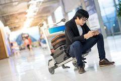 Νέα ασιατική συνεδρίαση ατόμων στο καροτσάκι στο τερματικό αερολιμένων Στοκ φωτογραφία με δικαίωμα ελεύθερης χρήσης