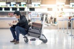 Νέα ασιατική συνεδρίαση ατόμων στο καροτσάκι στο τερματικό αερολιμένων Στοκ Φωτογραφία
