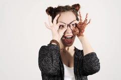Νέα αστεία και χαριτωμένη γυναίκα hipster που χαμογελά και που αστειεύεται και που κάνει τα θεάματα από τα χέρια της Στοκ φωτογραφίες με δικαίωμα ελεύθερης χρήσης