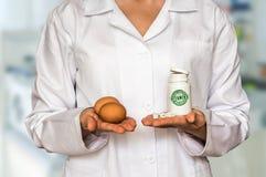 Νέα αυγά εκμετάλλευσης γιατρών και μπουκάλι των χαπιών με τις βιταμίνες και Στοκ φωτογραφίες με δικαίωμα ελεύθερης χρήσης