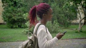 Νέα αφρικανική γυναίκα με το τηλέφωνο εκμετάλλευσης σακιδίων πλάτης και μετάβαση στο πανεπιστήμιο, σπουδαστής με τα ρόδινα dreadl απόθεμα βίντεο