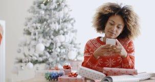 Νέα αφρικανική γυναίκα που ελέγχει για τα μηνύματα Χριστουγέννων Στοκ Εικόνες