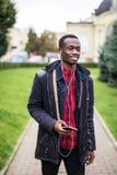 Νέα αφρικανική μουσική ακούσματος ατόμων στα μεγάλα ακουστικά Χαλάρωση σπουδαστών, να ονειρευτεί έξυπνα τηλέφωνο εκμετάλλευσης κα Στοκ φωτογραφία με δικαίωμα ελεύθερης χρήσης