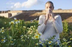 Νέα αλλεργική γυναίκα που φτερνίζεται σε ένα λιβάδι Στοκ Φωτογραφία