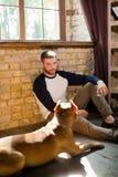 Νέα βάναυση συνεδρίαση ατόμων στο πάτωμα με το τεριέ Staffordshire του στοκ εικόνες με δικαίωμα ελεύθερης χρήσης