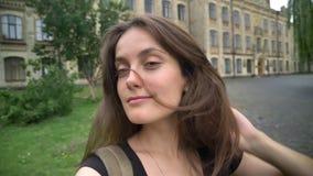 Νέα βέβαια όμορφη γυναίκα που παίρνει selfie και που εξετάζει τη κάμερα, που στέκεται στο πάρκο κοντά στο κολλέγιο φιλμ μικρού μήκους