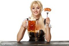 Νέα βαυαρική γυναίκα στη συνεδρίαση dirndl στον πίνακα με την μπύρα στο άσπρο υπόβαθρο Στοκ Εικόνα