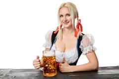 Νέα βαυαρική γυναίκα στη συνεδρίαση dirndl στον πίνακα με την μπύρα στο άσπρο υπόβαθρο Στοκ Εικόνες