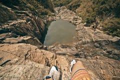 Νέα γενναία συνεδρίαση ατόμων σε έναν υψηλό απότομο βράχο πετρών επάνω από λίγη λίμνη Τοπ όψη Στοκ Εικόνες