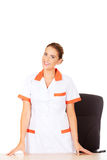 Νέα γιατρός ή νοσοκόμα θηλυκών χαμόγελου που στέκεται πίσω από το γραφείο Στοκ εικόνα με δικαίωμα ελεύθερης χρήσης