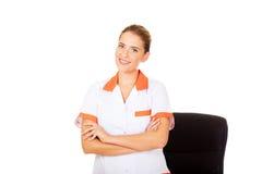 Νέα γιατρός ή νοσοκόμα θηλυκών χαμόγελου που στέκεται πίσω από το γραφείο Στοκ Εικόνες