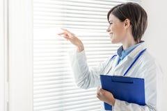 Νέα γιατρός ή νοσοκόμα που κοιτάζει μέσω ενός παραθύρου στοκ φωτογραφία με δικαίωμα ελεύθερης χρήσης