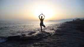 Νέα γιόγκα άσκησης γυναικών στην παραλία στο ηλιοβασίλεμα απόθεμα βίντεο