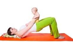 Νέα γιόγκα άσκησης μητέρων γυναικών με το μωρό Στοκ φωτογραφίες με δικαίωμα ελεύθερης χρήσης