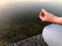 Νέα γιόγκα πρακτικών γυναικών και meditates στη θέση λωτού Στοκ Φωτογραφία