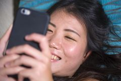 Νέα γλυκιά ευτυχής και αρκετά ασιατική κορεατική γυναίκα που χρησιμοποιεί τα κοινωνικά μέσα app Διαδικτύου στο κινητό τηλέφωνο πο Στοκ Φωτογραφία