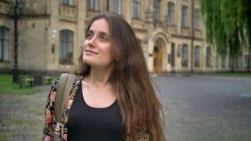 Νέα γοητευτική γυναίκα που κοιτάζει γύρω από και που στέκεται στο πάρκο κοντά στο κολλέγιο, ευτυχής και εύθυμος φιλμ μικρού μήκους