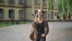 Νέα γοητευτική γυναίκα που πηγαίνει μακρυά από το κολλέγιο και την ομιλία στο τηλέφωνο κυττάρων, τη φθορά του ζωηρόχρωμου σακακιο απόθεμα βίντεο