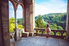 Νέα γοητευτική κυρία στο εκλεκτής ποιότητας φόρεμα στο μπαλκόνι του κάστρου στοκ εικόνες με δικαίωμα ελεύθερης χρήσης