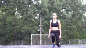 Νέα γυναίκα αθλητών στην αθλητική εξάρτηση που συμμετέχεται στην ικανότητα στον αθλητικό τομέα στο πάρκο φιλμ μικρού μήκους