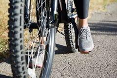 Νέα γυναίκα αθλητική σε ένα ποδήλατο βουνών Στοκ Εικόνες