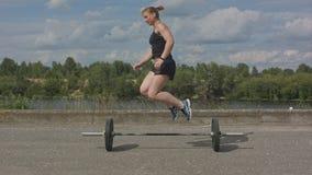 Νέα γυναίκα αντλιών σωμάτων που επιλύει τις ασκήσεις άκρης με το barbell Στοκ φωτογραφίες με δικαίωμα ελεύθερης χρήσης
