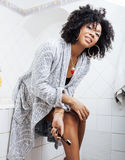 Νέα γυναίκα αφροαμερικάνων ομορφιάς στο μπουρνούζι με την οδοντόβουρτσα που παίρνει την προσοχή πρωινού της, έννοια τρόπου ζωής Στοκ Φωτογραφία