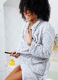 Νέα γυναίκα αφροαμερικάνων ομορφιάς στο μπουρνούζι με την οδοντόβουρτσα Στοκ φωτογραφίες με δικαίωμα ελεύθερης χρήσης