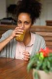 Νέα γυναίκα αφροαμερικάνων που πίνει το χυμό από πορτοκάλι στοκ εικόνα