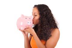 Νέα γυναίκα αφροαμερικάνων που φιλά τη piggy τράπεζα Στοκ φωτογραφία με δικαίωμα ελεύθερης χρήσης
