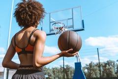 νέα γυναίκα αφροαμερικάνων στον αθλητικό στηθόδεσμο που κρατά μια σφαίρα καλαθοσφαίρισης στοκ φωτογραφίες