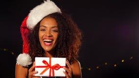 Νέα γυναίκα αφροαμερικάνων στο φόρεμα κομμάτων και κιβώτιο δώρων εκμετάλλευσης καπέλων Santa με την κόκκινη κορδέλλα στο μαύρο υπ φιλμ μικρού μήκους