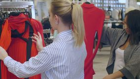 Νέα γυναίκα βοήθειας καταστημάτων βοηθητική στο shoose ένα φόρεμα στη λεωφόρο φιλμ μικρού μήκους