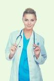 Νέα γυναίκα γιατρών με το στηθοσκόπιο που παρουσιάζει κάτι, που απομονώνεται στο άσπρο υπόβαθρο στοκ εικόνες