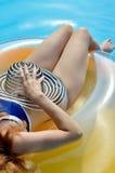 Νέα γυναίκα γοητείας με ένα λαστιχένιο δαχτυλίδι στην πισίνα Στοκ Φωτογραφίες