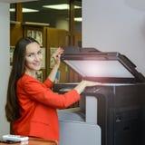 Νέα γυναίκα γραμματέων που κάνει τις φωτοτυπίες στο γραφείο στοκ εικόνες με δικαίωμα ελεύθερης χρήσης