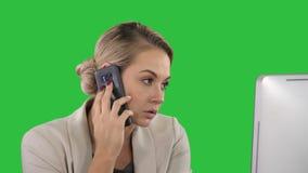 Νέα γυναίκα γραφείων που μιλά σε κάποιο στο κινητό τηλέφωνό της σε μια πράσινη οθόνη, κλειδί χρώματος απόθεμα βίντεο