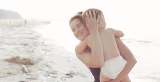 Νέα γυναίκα εμβλημάτων mom που κρατά ένα αγοράκι υπαίθρια στοκ φωτογραφίες με δικαίωμα ελεύθερης χρήσης
