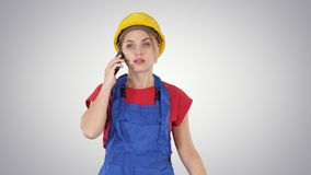Νέα γυναίκα εργαζόμενος που μιλά στο τηλέφωνο περπατώντας στο υπόβαθρο κλίσης απόθεμα βίντεο