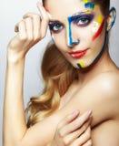 Νέα γυναίκα ζωγράφος με το ακρυλικό χρώμα στο πρόσωπο Στοκ Φωτογραφία