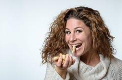 Νέα γυναίκα διασκέδασης με ένα φυστίκι στο στόμα της στοκ εικόνα