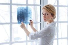 Νέα γυναίκα ιατρών που δείχνει στην ακτίνα X Στοκ φωτογραφία με δικαίωμα ελεύθερης χρήσης