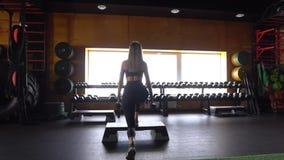 Νέα γυναίκα ικανότητας που κάνει τη στάση οκλαδόν με τους αλτήρες στα χέρια Σκηνή στη γυμναστική Γυναίκα sportswear με τους αλτήρ απόθεμα βίντεο