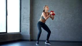 Νέα γυναίκα ικανότητας που κάνει τη στάση οκλαδόν με τους αλτήρες στα χέρια Σκηνή στη γυμναστική φιλμ μικρού μήκους