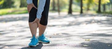Νέα γυναίκα ικανότητας που κρατά τον τραυματισμό αθλητικών ποδιών του, μυς επίπονος κατά τη διάρκεια της κατάρτισης Ασιατικός δρο στοκ φωτογραφία