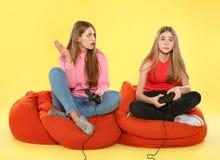 Νέα γυναίκα και έφηβη που παίζουν τα τηλεοπτικά παιχνίδια με τους ελεγκτές στοκ εικόνες
