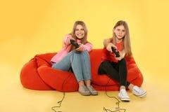 Νέα γυναίκα και έφηβη που παίζουν τα τηλεοπτικά παιχνίδια με τους ελεγκτές στοκ φωτογραφίες