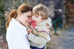 Νέα γυναίκα και λίγος γιος που αγκαλιάζουν στο φως βραδιού Στοκ φωτογραφία με δικαίωμα ελεύθερης χρήσης