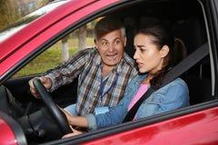 Νέα γυναίκα και ανώτερος εκπαιδευτικός στο αυτοκίνητο Αποτύχετε τον οδηγώντας διαγωνισμό στοκ εικόνες